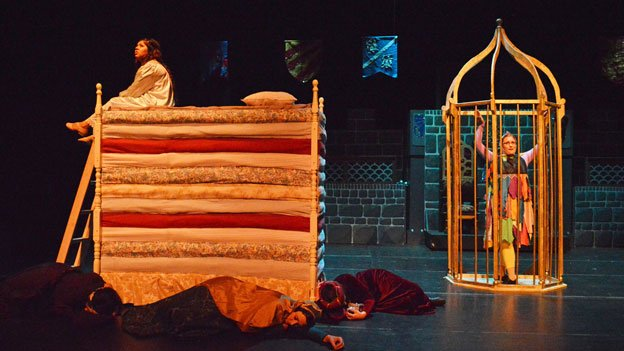 Princess Winnifred (Carla Astudillo) can't sleep a wink with a pea hidden beneath her mattress.
