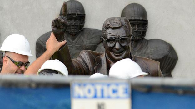 Workers handle the statue of former Penn State football coach Joe Paterno before removing the statue Sunday, July 22, 2012. Paterno's wins were vacated by the NCAA this morning in the wake of the sex abuse allegations against assistant coach Jerry Sandusky