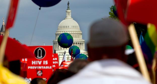 People hold signs and balloons as they participate in the AIDS March in Washington on Sunday.