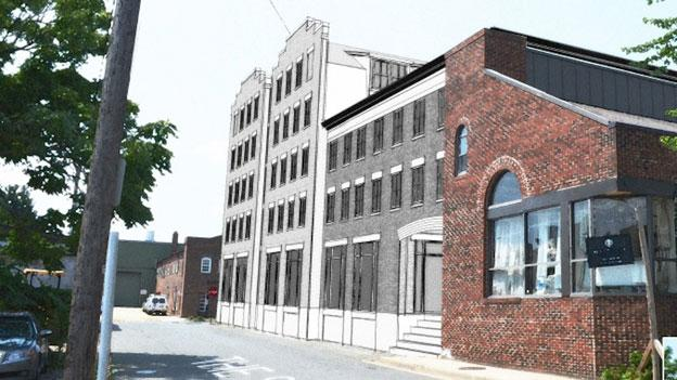 Carr Hospitality has created a concept plan for a new hotel on the waterfront, shown here in black and white adjacent to an existing building on Strand Street in Old Town.