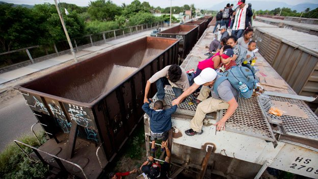 A young boy is is helped down from the top of a freight car, as Central Americans board a northbound freight train in Ixtepec, Mexico, Saturday, July 12, 2014. The number of unaccompanied minors detained on the U.S. border has more than tripled since 2011. Children are also widely believed to be crossing with their parents in rising numbers.