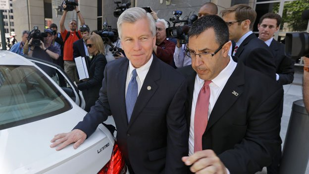 Former Virginia Gov. Bob McDonnell, left, is escorted out of Federal court by a security officer after a motions hearing in Richmond, Va., Monday, May 19, 2014.