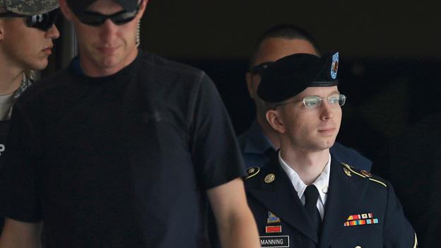 Army Pfc. Bradley Manning is escorted out of a courthouse in Fort Meade, Md., after receiving a verdict in his court martial.