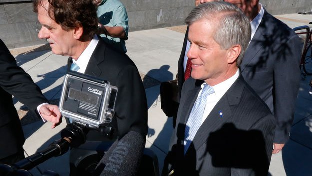 Former Virginia Gov. Robert F. McDonnell, center, with his attorney Henry W. Asbill, left, arrives at the federal courthouse in Richmond, Va., Monday, July 28, 2014, on the first day of jury selection in the corruption trial of former McDonnell and his wife in Richmond, Va.