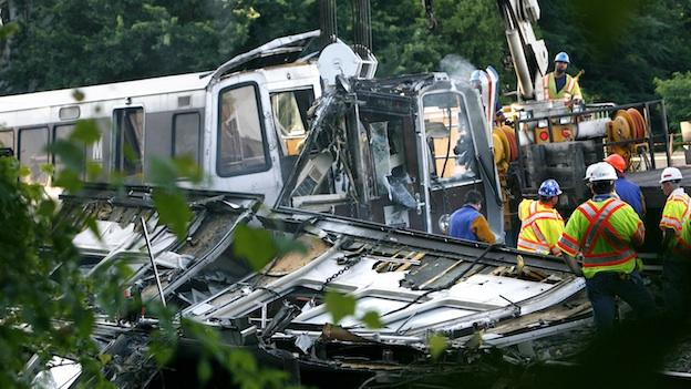 In this file photo from June 23, 2009 officials continue to work around the scene of a rush-hour collision between two Metro transit trains in northeast Washington, D.C. Federal investigators are urging Metro on Monday July 13, 2009, to continuously monitor its computerized train control system following the deadly crash.
