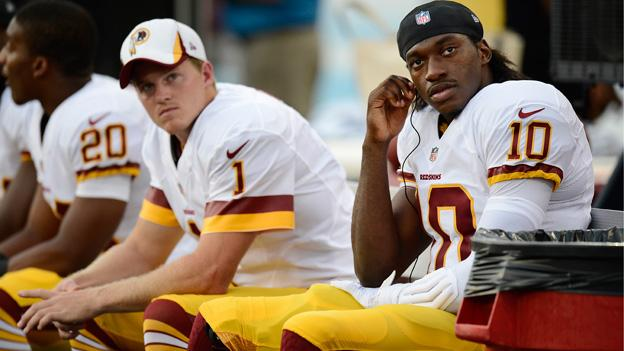 Washington Redskins quarterback Robert Griffin III (10) and kicker John Potter (1) watch from the bench in the first quarter of a preseason NFL football game between the Redskins and the Tennessee Titans on Thursday, Aug. 8, 2013, in Nashville, Tenn.