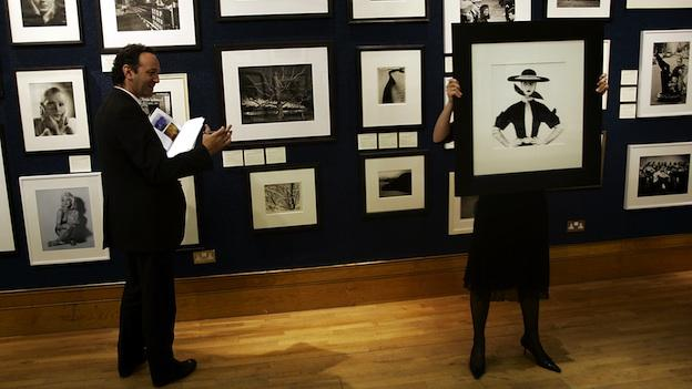 A collector, left, makes a comment as a Christie's auction house worker holds Irving Penn's classic image of Jean Patchet that appeared at the Vogue magazine' cover in 1950, during a presentation in London, Friday May 13, 2005.