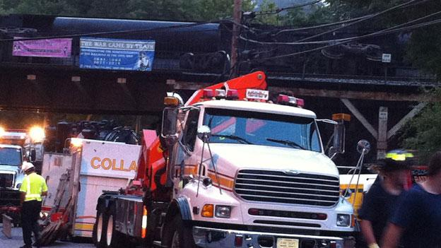 A derailment caused train cars to fall off a bridge over historic Main St. in Ellicott City, Md.