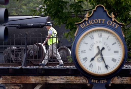 An official walks past part of a CSX freight trail that derailed in Ellicott City, Md., Tuesday, Aug. 21.