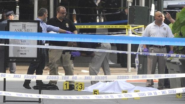 Police lean over a sheet covered body on Fifth Avenue as they investigate a multiple shooting outside the Empire State Building, Friday, Aug. 24, 2012, in New York.