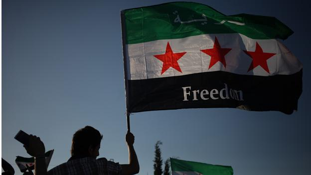 A Syrian protester waves the Syrian revolutionary flag, during a protest in front of the Syrian embassy to condemn the alleged poison gas attack on the suburbs of Damascus, during a protest in front of the Syrian embassy, in Amman, Jordan.