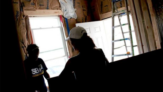 Volunteers with the St. Bernard Project work to install drywall.