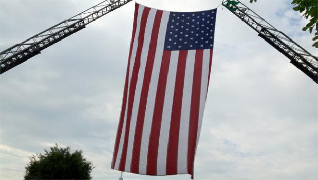 The American flag flew between a pair of cranes
