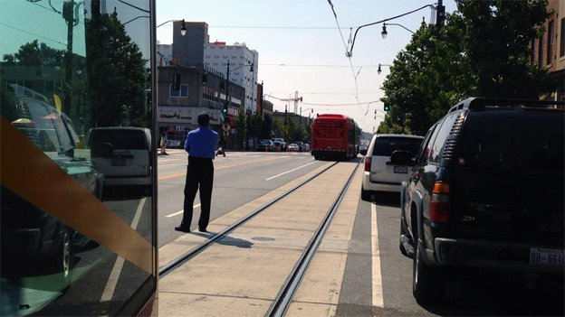 A streetcar operator searches for the driver of a white van that is blocking the lane on H Street Northeast.