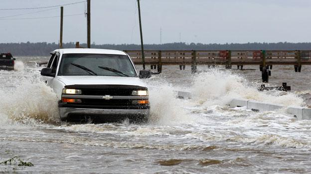 A motorist drives through a flooded street as waves ahead of Isaac break over the road way  Tuesday, Aug. 28, 2012, in Bay St. Louis, Miss.