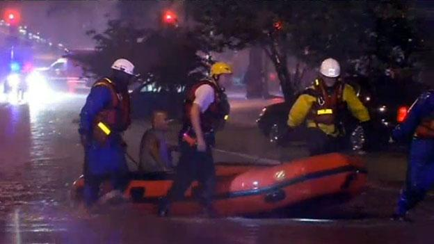 A rescue crew pulls a man to safety after his car became stuck in floodwaters in Northwest D.C. Sunday, Sept. 2.