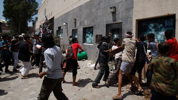 Yemeni protestors break windows of the U.S. Embassy during a protest about a film ridiculing Islam's Prophet Muhammad, in Sanaa, Yemen, Thursday, Sept. 13, 2012.