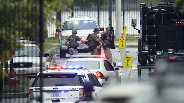Law enforcement personnel are seen through the gate into the Washington Navy Yard in Washington, Monday, Sept. 16, 2013. At least one gunman opened fire inside a building at the Washington Navy Yard on Monday morning, and officials said several people were killed and more were wounded, including a law enforcement officer.