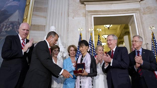Myanmar democracy leader Aung San Suu Kyi, center, receives the Congressional Gold Medal from Speaker of the House John Boehner, at the U.S. Capitol in Washington, Wednesday, Sept. 19, 2012.
