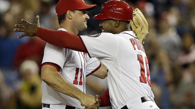 Washington Nationals third base coach Bo Porter (16) embraces third baseman Ryan Zimmerman (11) after their 4-1 win over the Los Angeles Dodgers, earning them a playoff spot, during their baseball game at Nationals Park, in Washington, Thursday, Sept. 20, 2012.