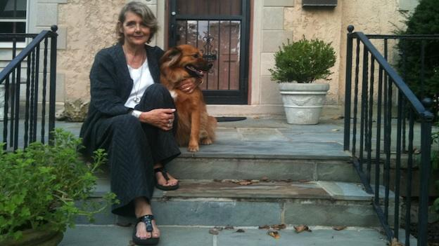 Tamora Ilasat sits outside her Woodley Park home with her dog.