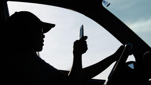 A driver uses a cell phone to text while driving.