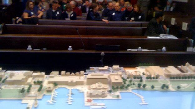 A model of the Alexandria waterfront shows changes as citizens wait to speak at a public hearing.