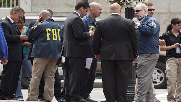 Washington Police and FBI agents gather outside the Family Research Council in Washington, Wednesday, Aug. 15, 2012, after security guard at the lobbying group was been shot in the arm.