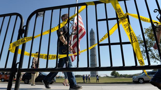 Pedestrians walk past a barricade preventing them from entering the World War II Memorial during the shutdown on Oct. 2.