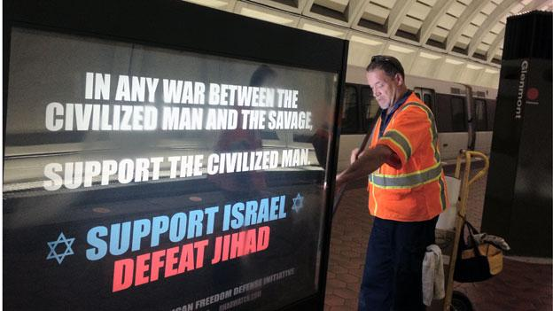 A WMATA employee posts one of the anti-Islamic billboards in the Glenmont Metro station. The ads have provoked a range of responses this week.