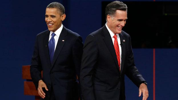President Barack Obama walks past Republican presidential nominee Mitt Romney during the first presidential debate at the University of Denver.