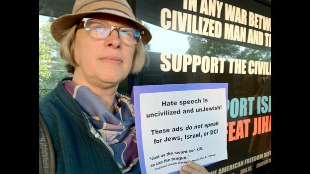 Virginia Spatz holds a sign quoting the talmud as she protests the sign placed by the American Freedom Defense Initiative.