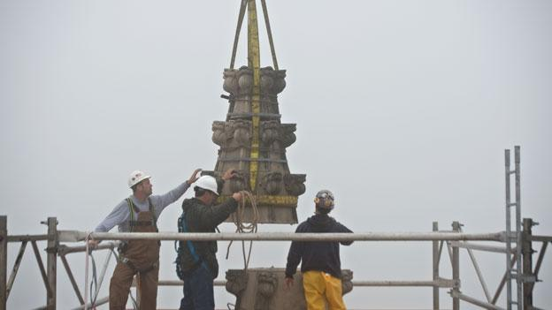 Engineers attach part of a pinnacle from the National Cathedral to be lowered by a crane for repairs after the August quake. Total repairs are now expected to cost $20 milion.