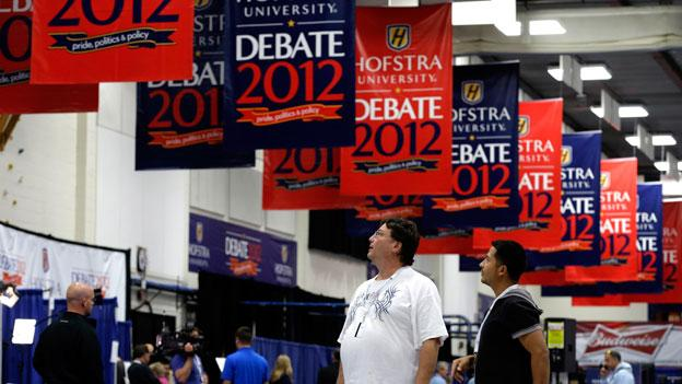 Billy Koske, left, and Jose Reyes look at signs hanging in the media filing center before Tuesday's presidential debate between President Barack Obama and Republican presidential candidate, former Massachusetts Gov. Mitt Romney at Hofstra University in Hempstead, N.Y.