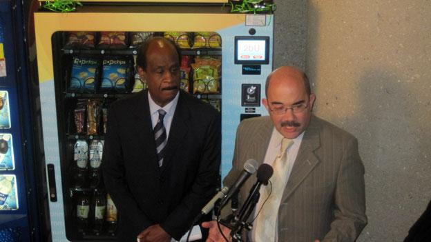 Montgomery County executive Isiah Leggett, left, and Council member George Leventhal stand in front of the new vending machine in the county office building in Rockville.