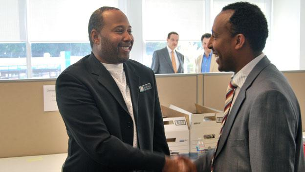 Esayas Ayele, right, getting hired by 7-Eleven representative Mark Crist at a city-sponsored One City, One Hire employment event.