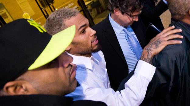 Singer Chris Brown is surrounded by bodyguards as he departs the H. Carl Moultriel courthouse Monday, Oct. 28, 2013, with one of his attorney's, Danny Onorato, second from right, in Washington.