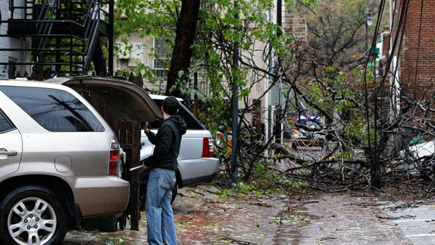 Jeff Stomel, 26, of Washington, loads his car with bottled water in an alley between U Street and Willard Street NW, where tree branches fell on cable lines and a car during Hurricane Sandy, in Washington, on Tuesday, Oct. 30, 2012.