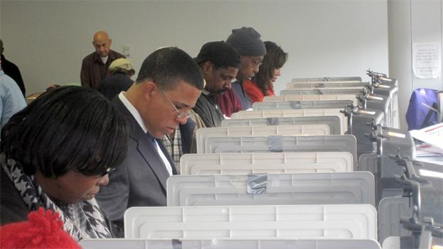 Lt. Gov. Anthony Brown, second from the left, casts his early ballot Wednesday at the County's Sports & Learning Center in Landover, Md.