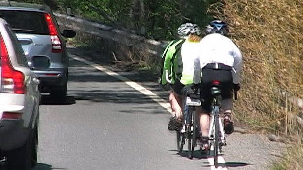 Cyclists don't have to hug the rail — they are allowed to occupy the road just like cars.