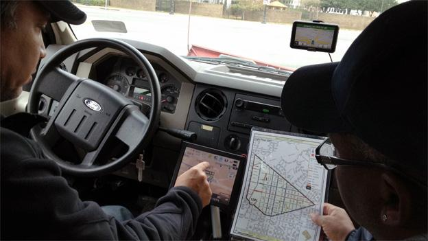 District Department of Public Works drivers compare old paper map to new electronic map that shows the streets they've plowed or salted.