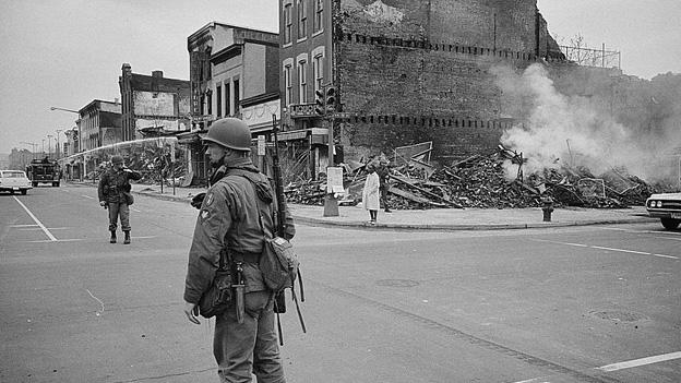 A soldier standing guard in a Washington, D.C., street with the ruins of buildings that were destroyed during the riots that followed the assassination of Martin Luther King, Jr.