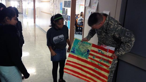 Army Brig. General William Cole receives a flag from the 6th grade class.