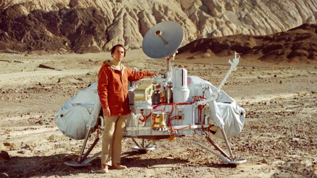 Carl Sagan with a model of the Viking lander.