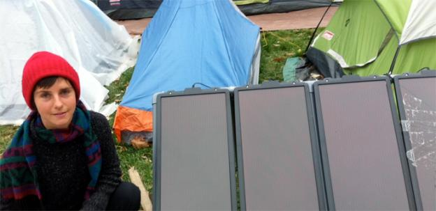 Occupy DC activist Kelsey Tribble with one of the donate solar panels that powers their media tent.