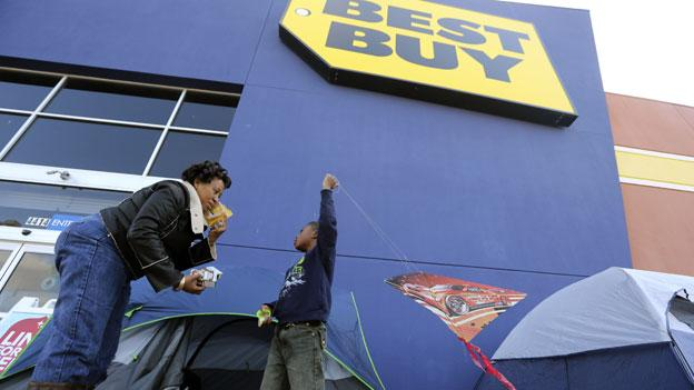Denise Smith-Lad, left, asks her grandson Jordan Smith, 6, what he would like to eat as they camp in front of a Best Buy store in Cockrell Hill, Texas, Monday, Nov. 19, 2012. Smith and her family have come early to line up for the the shopping deals available the day after Thanksgiving.
