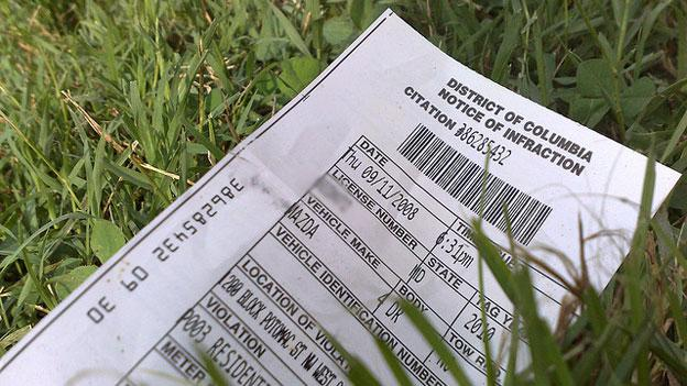 A D.C. parking ticket that has been discarded in the grass.