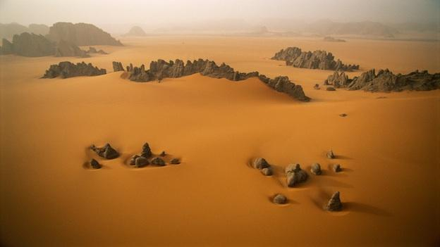 Sandstone pinnacles rise through the orange sand dunes of Karnasai Valley in Chad.