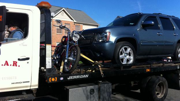 A tow truck drives off with an SUV and a motorcycle confiscated from D.C. Council member Harry Thomas Jr.'s garage Dec. 2.