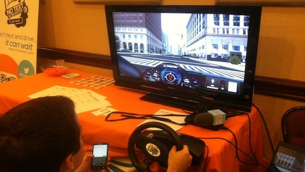 WAMU 88.5 reporter Martin DiCaro tests a distracted driving simulator at a summit in Washington, D.C.